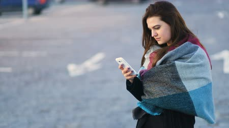 Young smiling beatiful business girl woman in black coat with rug on shoulders speak with someone with the smartphone. Steady cam, slow mo shot, two shots Stock mozgókép
