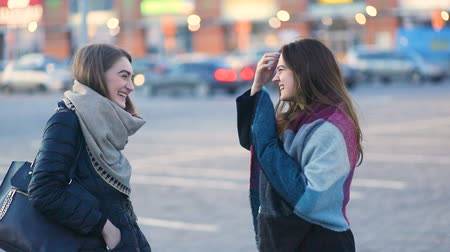 Two young attractive girls laughing and smiling on the urban street in front of the huge building. Steady cam, slow mo shot Stock mozgókép