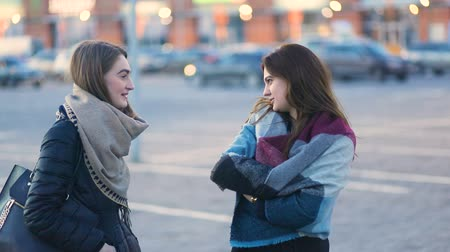 Two young beatiful pretty student stylish girls talking and laughing on the urban street near the cars, Steady cam, slow mo shot