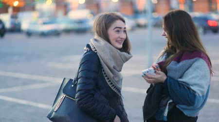 Two brown-haired fashionable attractive student girls with long hair talking, laughing and hugging on the parking, Steady cam, slow mo shot Stock mozgókép