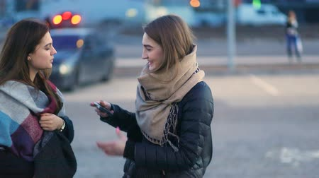 Two pretty young stylish glamorous women staying on the parking, talking, laughing and tapping the phone, Steady cam, slow mo shot