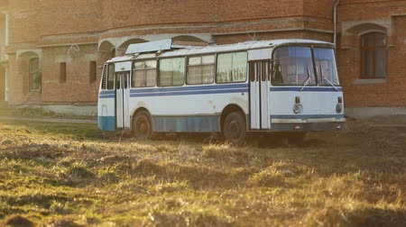 minibus : Old vintage white blue soviet union ussr relic bus in sunny summer day in field in front of yellow orange brick wall, Steady cam, slow mo shot