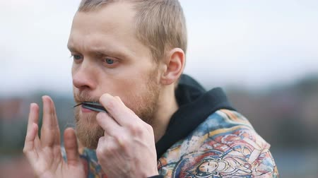 Closeup young smart man with beige beard playing on lips musical instrument in landscape of countryside, Steady cam, slow mo shot Stock mozgókép