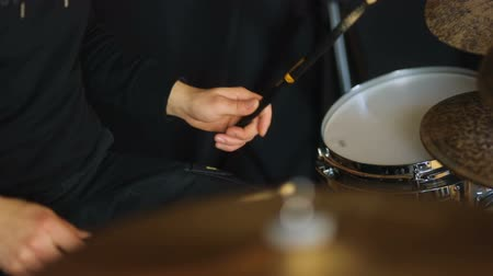 ритм : Man in shadeless black style playing on the drums side-view
