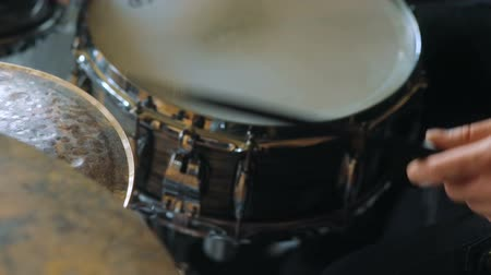 baqueta : Side-view closeup of man playing drums in studio