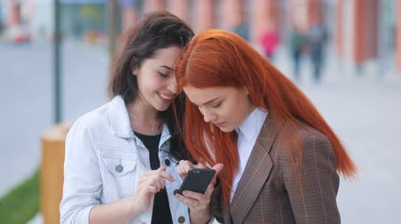 fiatalos : Two beatiful youthful girls weared in business style with swaying wind in the hair laughing and looking in smartphone with urban landscape background Steadicam slow motion video