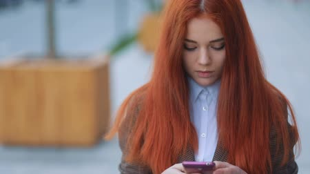 transmitting : Frontal view of young beatiful attractive red-haired businness girl in brown jacket and white t-shirt staying on the street and communicating via smartphone, urban landscape in background
