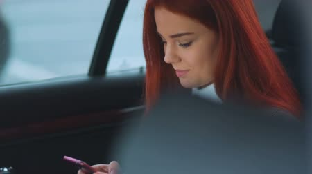 auta : Fantastic attractive young red-haired girl with smartphone smiling and sitting on the back seat of the car using her phablet smartphone