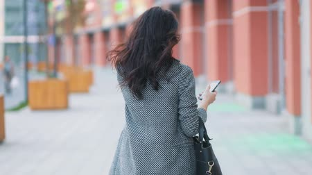 phablet : Back span of the young tender amazing business girlin strict gray jacket and black dress model walking on the urban busy street with phablet smartphone in her hand Steadicam slow motion shot