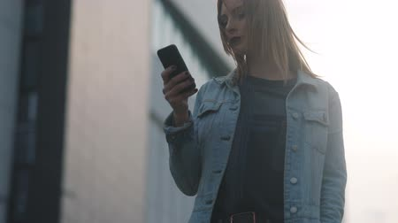 térképészet : Shot of fashion young beautiful model student girl with dark-red lips in blue denim court and strict bluseusing her smartphone on the urban background. Steadicam slow motion shot Stock mozgókép