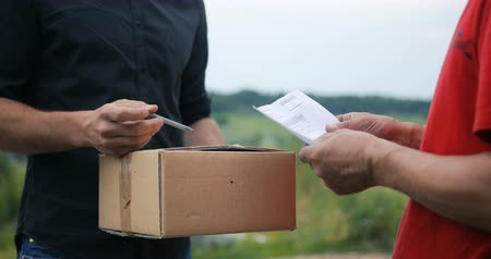 pošta : Man hands accepting a delivery of boxes from deliveryman, countryside field background courier
