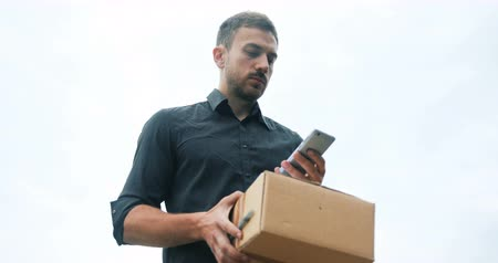 почтальон : Courier delivery with parcel using mobile phone, speaking waiting for client