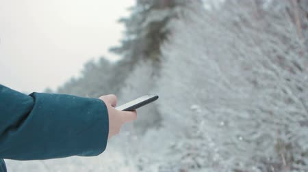 soczewki kontaktowe : Girl surfing the internet in nature, using smartphone, camera movement. It is winter