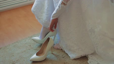 high heels : Bride Putting on Her White Shoes Stock Footage