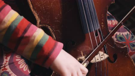 threadbare : kid playing old shabby cello