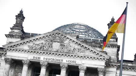 almanca : the german parliament building reichstag is shown isolated with a white background, a little wind is blowing in the flag, people are walking in the transparent dome of the building Stok Video