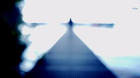 ileri : A male walks directly towards the camera on a footbridge. First only the outline is shining, to the end the whole person gets depth of field. Looks a little like space stuff, dimension change, rebirth, experience or similar.