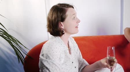 söyleme : Two women are talking on a red couch Stok Video