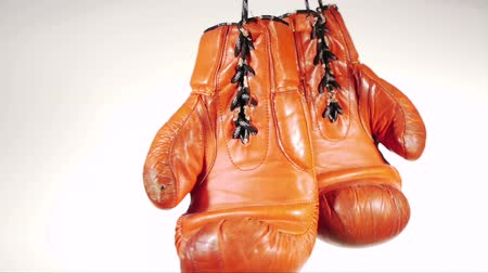 luva : a pair of boxing gloves is hung up and swings