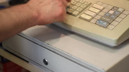 регистр : a man enters the amount of 1 and opens the drawer of a cash register