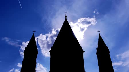 церковь : a church with three towers is shown, surrounded by a blue great sky with lots of clouds moving (time lapse)