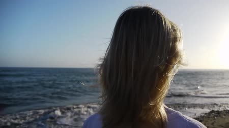 darbe : a woman waits on the beach and is looking at the sea Stok Video