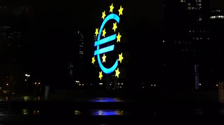euro : Clip shows the euro monument in the rain, located in Frankfurt before the tower of the european central bank, in the background some traffic is seen Stok Video