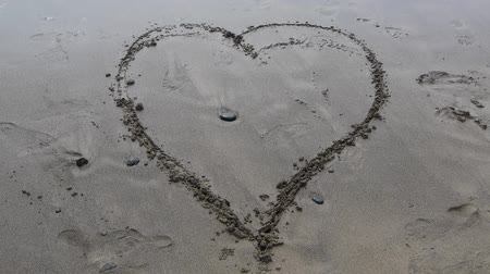романтика : a heart is painted in the sand of the beach, a wave removes the symbol Стоковые видеозаписи