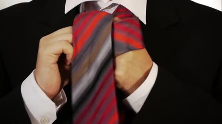 red tie : A male ably ties his tie with a knot.