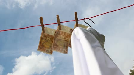 взятие : banknotes are waving in the wind on a clothesline beneath a white shirt Стоковые видеозаписи