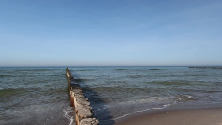 baltské moře : the Baltic Sea with waves, the beach shows the typical wooden stakes to break waves