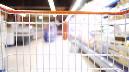 покупка товаров : a shopping cart is moving slowly through a super market Стоковые видеозаписи