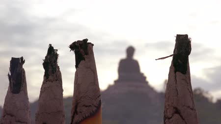 comemoração : foreground - incense sticks and incense sticks, in the background the silhouette of a Buddha statue on Lantau, Hong Kong Stock Footage