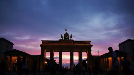 spousta : the berlin monument brandenburg gate with lots of people taking pictures at sunset time lapse scene