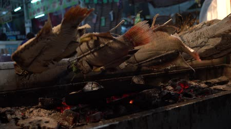 bracket : fish w salt crust is turning on a charcoal BBQ Stock Footage