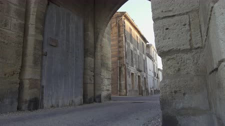 Panning shot - Gate of the fortress of Aigues Mortes in southern France - van coming into view