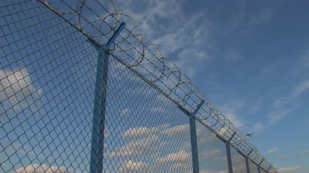 farpado : Plane passes with barbed wire fence in view at airport 1