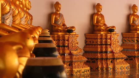 bálvány : Statues of golden buddhas sitting in a row.