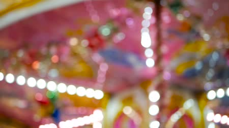 szédülés : Colorful blured merry background with defocused pink carousel and lights
