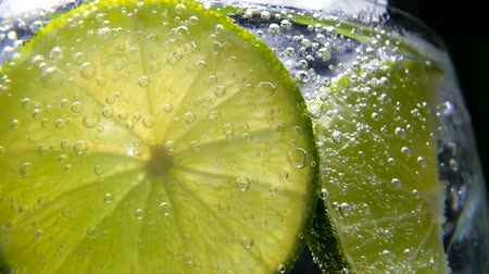citron : Macro close-up,refreshing soda tonic fizzy water, lime in Glass, ice. Slice of lemon, mineral bubbles. Detox or thirst concept. Healthy, dietary nutrition. Cold lemonade mojito drink. Black background