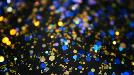 flitter : Defocused shimmering multicolored glitter confetti, black background. Party, magic, imagination. Rainbow colors, sparkle circles. Holiday abstract festive texture of shiny blurred bokeh light spots. Stock mozgókép