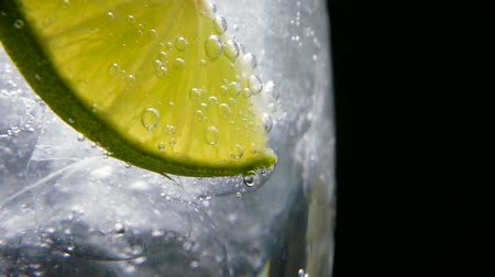 limonada : Macro close-up,refreshing soda tonic fizzy water, lime in Glass, ice. Slice of lemon, mineral bubbles. Detox or thirst concept. Healthy, dietary nutrition. Cold lemonade mojito drink. Black background