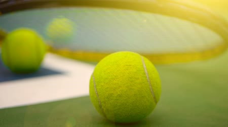 ütő : Close up of tennis equipment on the court. Sport, recreation concept. Yellow racket with a tennis ball in motion on a clay green blue court next to the white line with copy space and soft focus. Stock mozgókép