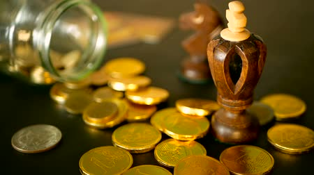 penny : Yellow coins fell out from jar. Symbol of investing, keeping money concept. Collecting cash conis in glass tin as moneybox. Close-up still life with gold coins on black table and rotating penny. Stock Footage