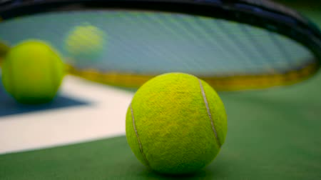 barro : Close up of tennis equipment on the court. Sport, recreation concept. Yellow racket with a tennis ball in motion on a clay green blue court next to the white line with copy space and soft focus. Stock Footage