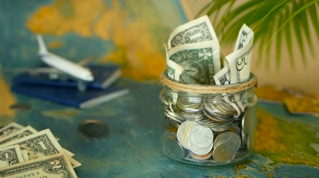 виза : Travel budget concept. Money saved for vacation in glass jar with world map, passport and plane. Banknotes and coins for adventure. Savings for journey. Collecting money for trip. Moneybox with cash.