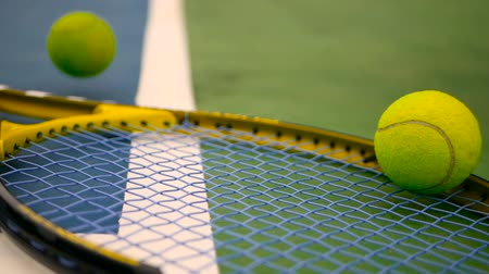 próximo : Close up of tennis equipment on the court. Sport, recreation concept. Yellow racket with a tennis ball in motion on a clay green blue court next to the white line with copy space and soft focus. Stock Footage