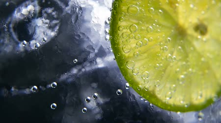 citrón : Macro close-up,refreshing soda tonic fizzy water, lime in Glass, ice. Slice of lemon, mineral bubbles. Detox or thirst concept. Healthy, dietary nutrition. Cold lemonade mojito drink. Black background