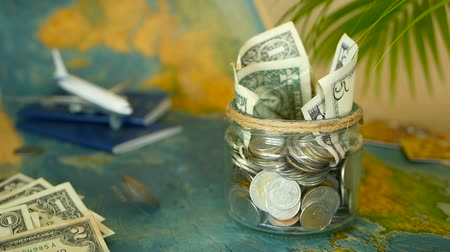 kumbara : Travel budget concept. Money saved for vacation in glass jar with world map, passport and plane. Banknotes and coins for adventure. Savings for journey. Collecting money for trip. Moneybox with cash.