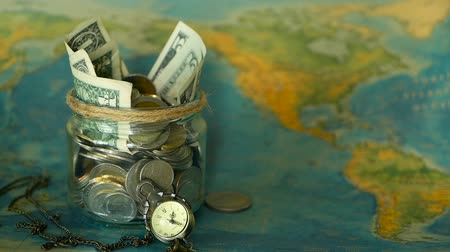 kumbara : Travel budget concept. Money saved for vacation in glass jar on world map background, copy space. Banknotes and coins for adventure. Savings for journey. Collecting money for trip. Moneybox with cash.